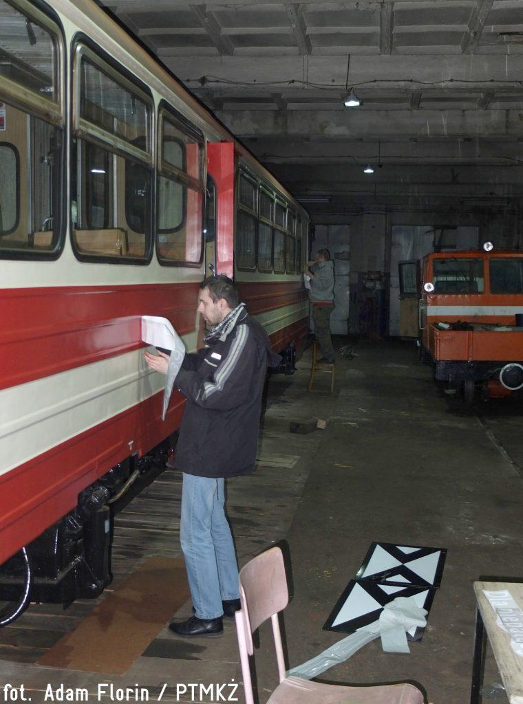 Wyklejanie oznaczeń zewnętrznych na wagonie motorowym MBxd2-212. Fot. Adam Florin.